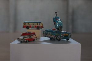 A toy tank, bus, and car made out of colorful tin, from the collection of Michael Luria